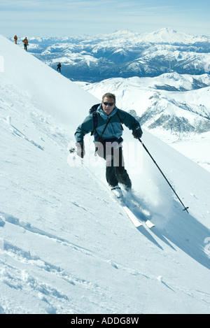 Skier skiing downhill, high angle view, mountains in background - Stock Photo