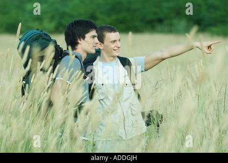 Two hikers standing in field, one pointing out of frame - Stock Photo