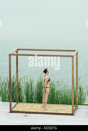 Young woman standing inside square structure, next to body of water - Stock Photo