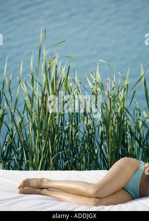 Woman lying on side, waist down, water and reeds in background - Stock Photo
