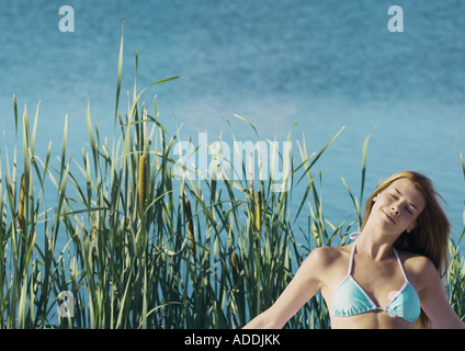 Young woman sunbathing, body of water in background - Stock Photo