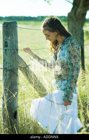 Young woman standing next to rural fence, looking down - Stock Photo