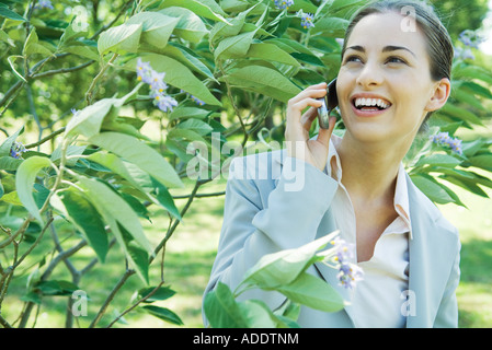 Businesswoman using cell phone outdoors, smiling - Stock Photo