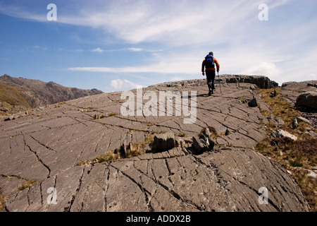 Hillwalker on mountainside in Snowdonia Rock shows striae or striation caused by glacier in Ice Age - Stock Photo