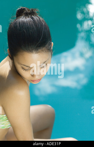 Young woman wearing bathing suit, pool in background, high angle view - Stock Photo