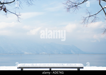 Snow-covered bench overlooking lake and mountains - Stock Photo