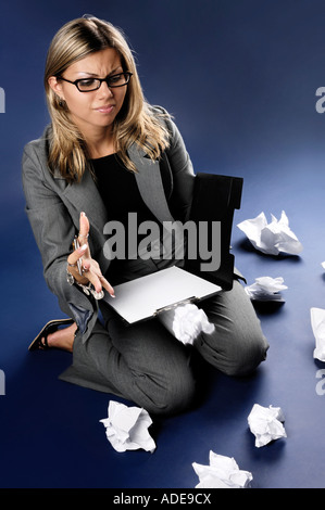 Irritated furious businesswoman throwing crampled paper on the floor - Stock Photo