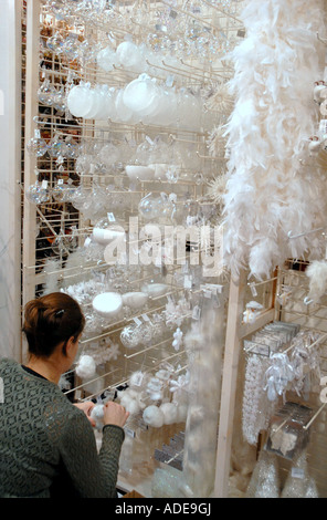 French Woman Kneeling Choosing White Christmas Decorations in Department Store The Paul Doumer Centre. Caen. Normandy. - Stock Photo