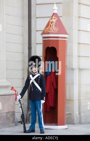 A Danish royal life guard stands outside Amalienborg Royal Palace, Copenhagen. - Stock Photo