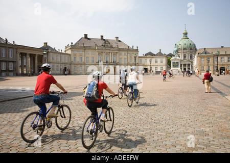 Cyclists on a sightseeing tour of Copenhagen visit Amalienborg Palace - Stock Photo