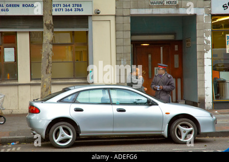 A man trying to get out of paying a parking ticket in Bethnal Green Road East London England UK - Stock Photo