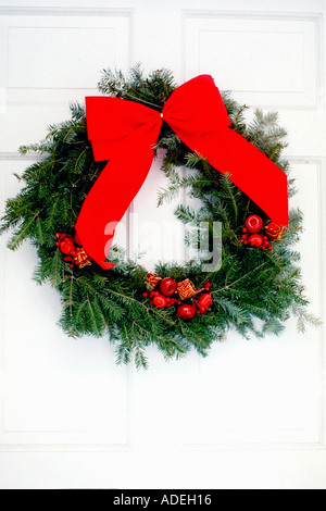 Closeup Still Life of a Christmas Wreath With A Red Velvet Bow Hanging on a White Door Copy Space - Stock Photo