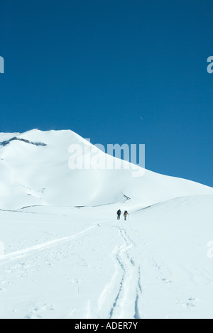 Skiers moving uphill in distance - Stock Photo