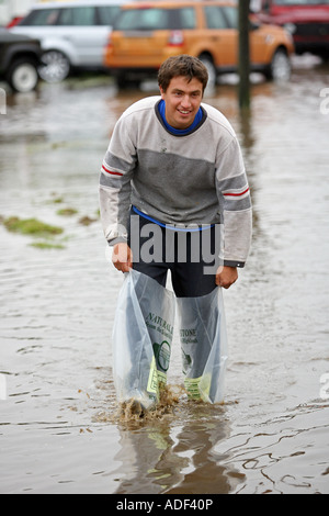 Boy splashes through flooded field with plastic bags on his feet after heavy rain near Turriff, Aberdeenshire, Scotland, - Stock Photo