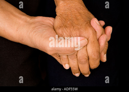 An old asian couple hold hands in a comforting or supporting manner - Stock Photo
