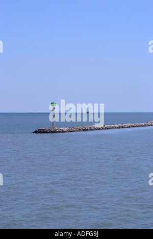Man-Made Breakwater with Marker Beacon at Entrance to Lewes Harbor with Harbor of Refuge Lighthouse in Background - Stock Photo