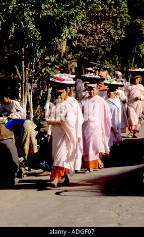 Nuns walking early in the morning looking for alms from the public - Stock Photo
