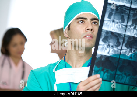 Doctor inspecting X rays - Stock Photo