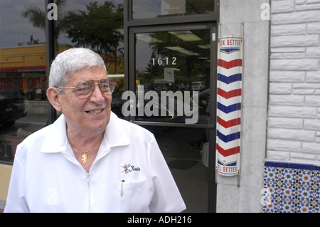 In Little Havana in Miami Florida on Calle Ocho 7th street in the afternoons Barber outside his shop - Stock Photo