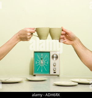 Caucasian male and female hands toasting with coffee cups across retro kitchen table setting - Stock Photo