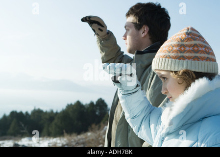 Young man and girl standing in snowy landscape, looking toward distance - Stock Photo