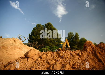 Soft ground just moved by an excavator which continues to dig in the background - Stock Photo