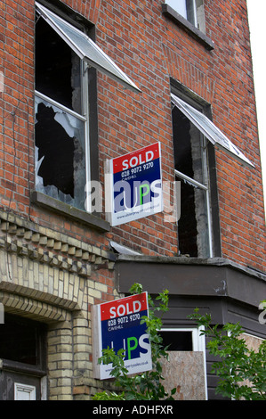 smashed broken windows of sold house with sold realtor sale signs outside - Stock Photo