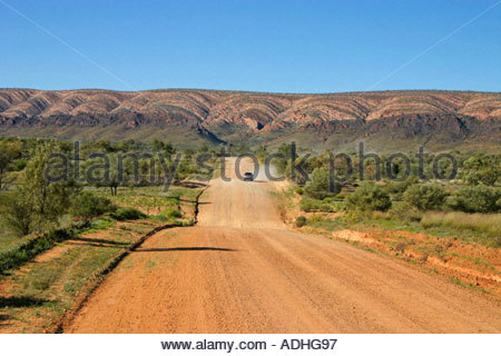Car approaching in the distance on the Namatjira Drive though the West MacDonnell Ranges in the Red Centre of Australia - Stock Photo