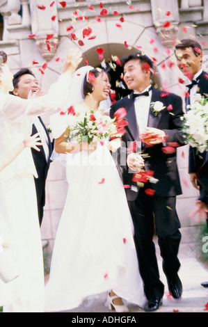 Flower petals being thrown on a bride and groom - Stock Photo