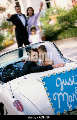 Portrait of a bride and her groom sitting in a convertible car - Stock Photo