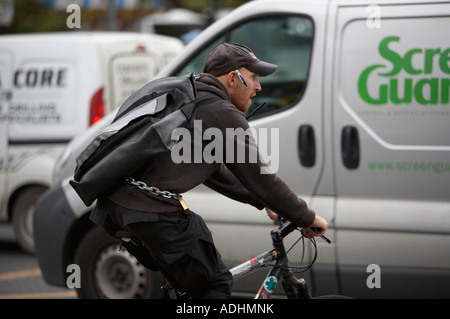 bicycle courier on bike cuts in and out of the traffic with pen in cap and chain round waist on the oconnell bridge - Stock Photo