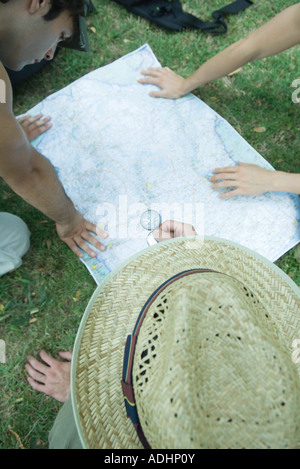 Hikers studying map, using compass - Stock Photo