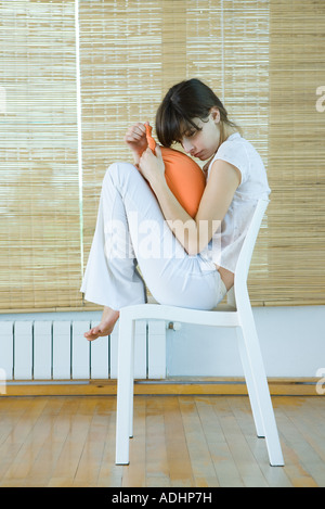 Young woman sitting on chair with knees up, holding cushion - Stock Photo