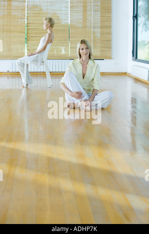 Group meditation, woman sitting on floor while second woman sits in chair - Stock Photo
