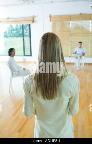 Group therapy, woman standing, facing men sitting in chairs, rear view - Stock Photo