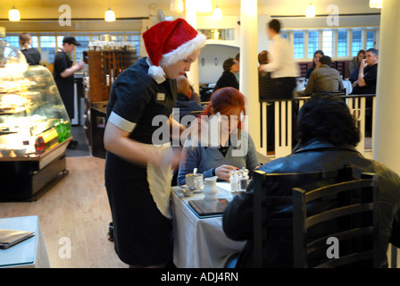 Waitress in Xmas Hat Serving Customers in The Willow Tea rooms, Designed by Charles Rennie Mackintosh 1904, Glasgow, - Stock Photo