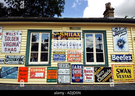Old fashioned enamel advertising signs dating from 1920 to 1960 on a Victorian station at a railway museum - Stock Photo