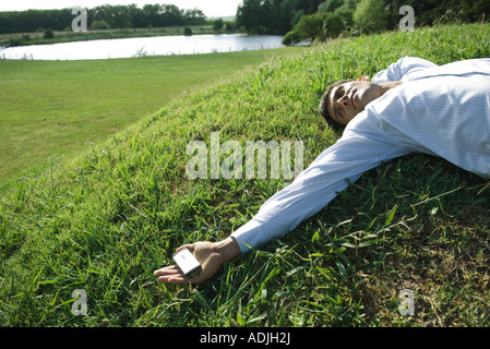 Businessman lying on grass, holding cell phone - Stock Photo