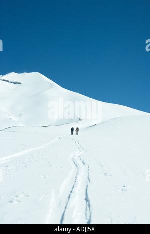 Skiers heading toward mountain, rear view - Stock Photo