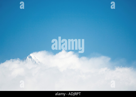 Snow-capped mountain surrounded by clouds - Stock Photo
