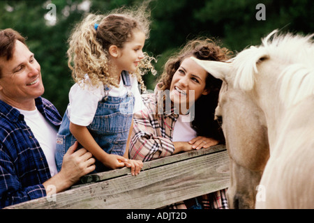 Parents with their daughter in front of a horse - Stock Photo