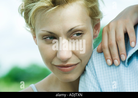 Woman leaning hand and head on man's shoulder, close-up - Stock Photo