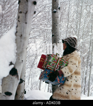 Young woman warmly dressed in rabbit fur coat with her arms full of Christmas gifts trudges through a snowstorm - Stock Photo
