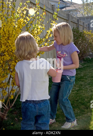 Young girls have found more treasures on their search for more Easter eggs in a backyard Easter egg hunt in Utah, - Stock Photo