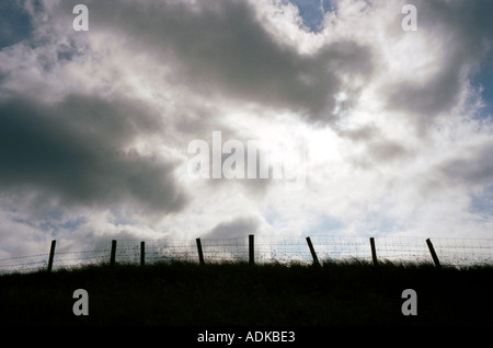 fence in countryside against dramatic sky - Stock Photo