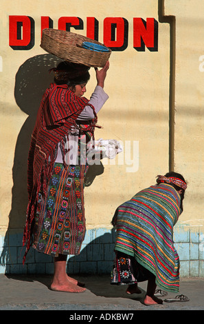 GUATEMALA Mother stops as her child pauses to slip her shoe on Walking from market Zunil Guatemala - Stock Photo