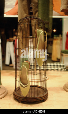 Woman's shoes hanging on cage in store front display window - Stock Photo