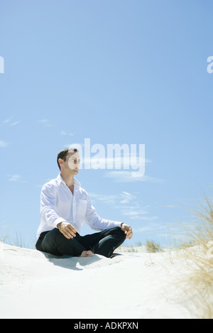 Man sitting indian style on dune - Stock Photo