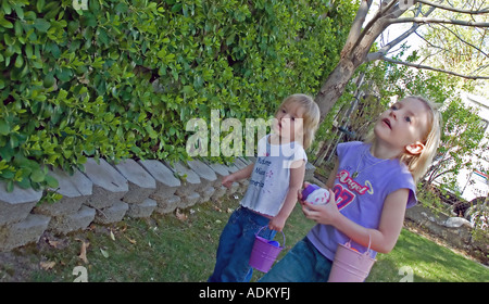 Young girls on the search for more Easter eggs in a backyard Easter egg hunt in Utah, USA. - Stock Photo