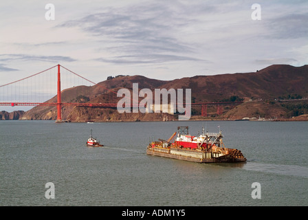 aerial above tug boat pulling loaded barge being towed toward the Golden Gate bridge - Stock Photo